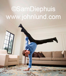 Man of Hispanic descent doing a handstand at home in his living room. Blue dress shirt and slacks.